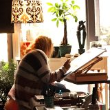 Monika Arturi painting watercolors in the studio